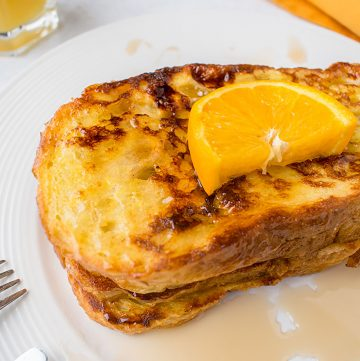 stack of French Toast with syrup and orange slice
