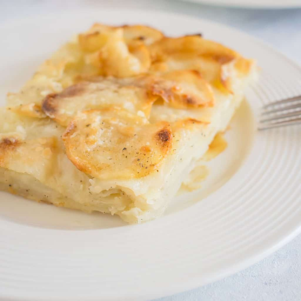 scalloped potatoes on white dish with fork