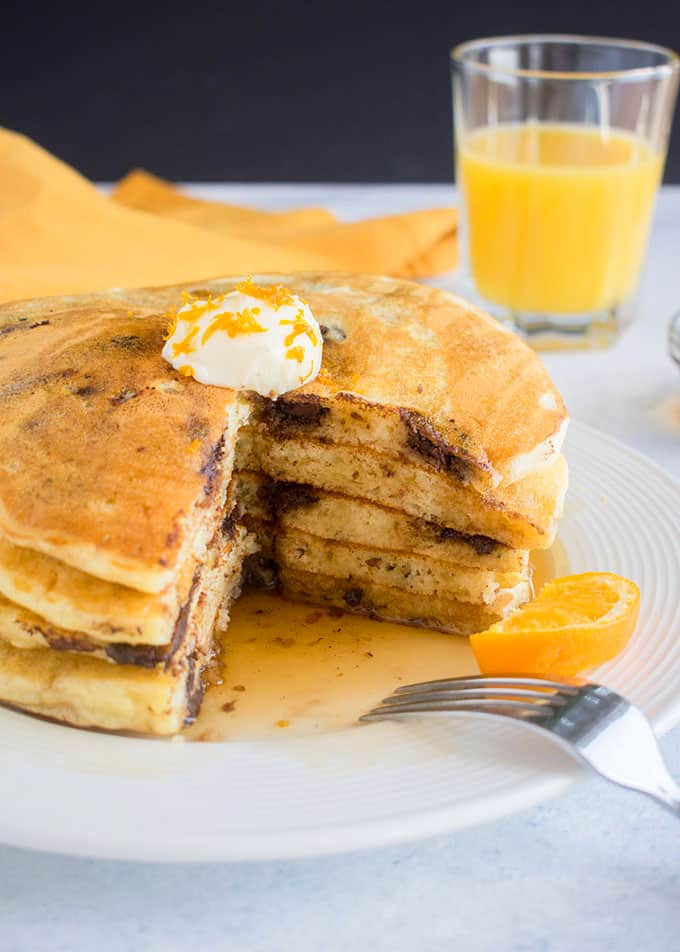 cut open stack of chocolate chip pancakes with butter and orange zest on top