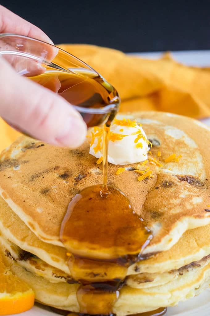 pouring syrup on stack of chocolate chip pancakes