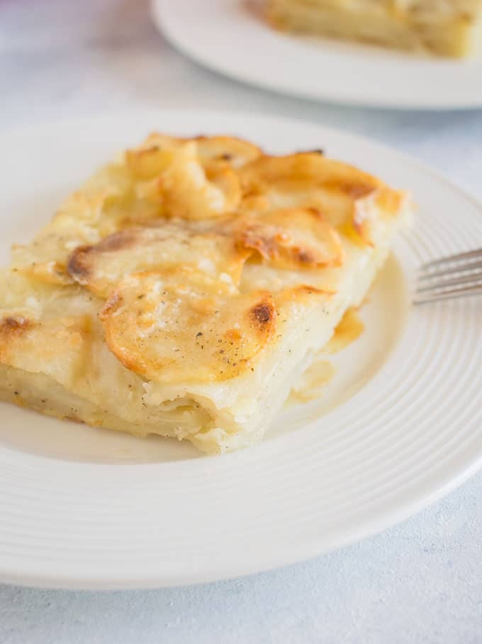 scalloped potatoes on a white plate with a fork