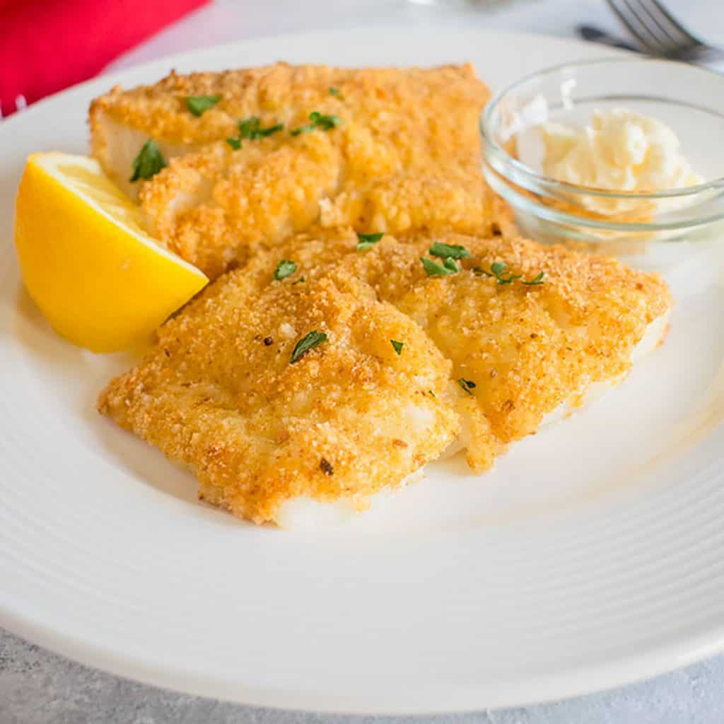 breaded fish on a plate with lemon and mayo