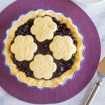 overhead view of whole blueberry pie with cookies on top