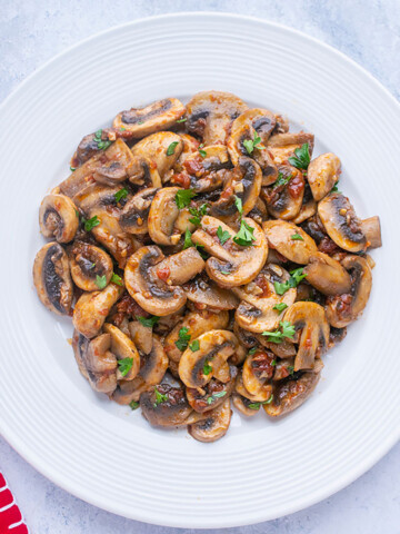 sliced cooked mushrooms on white plate, red napkin