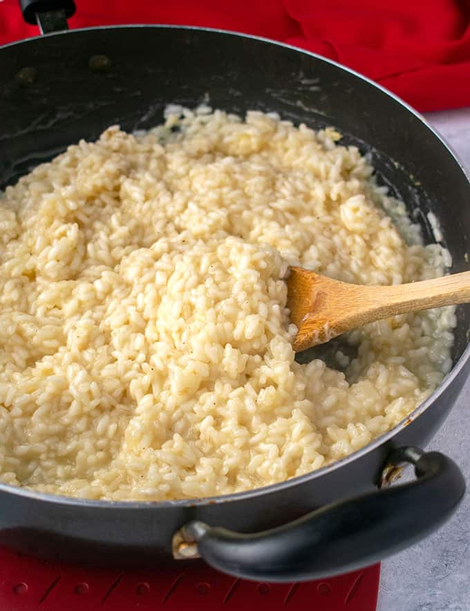 wooden spoonful of creamy rice in black pan