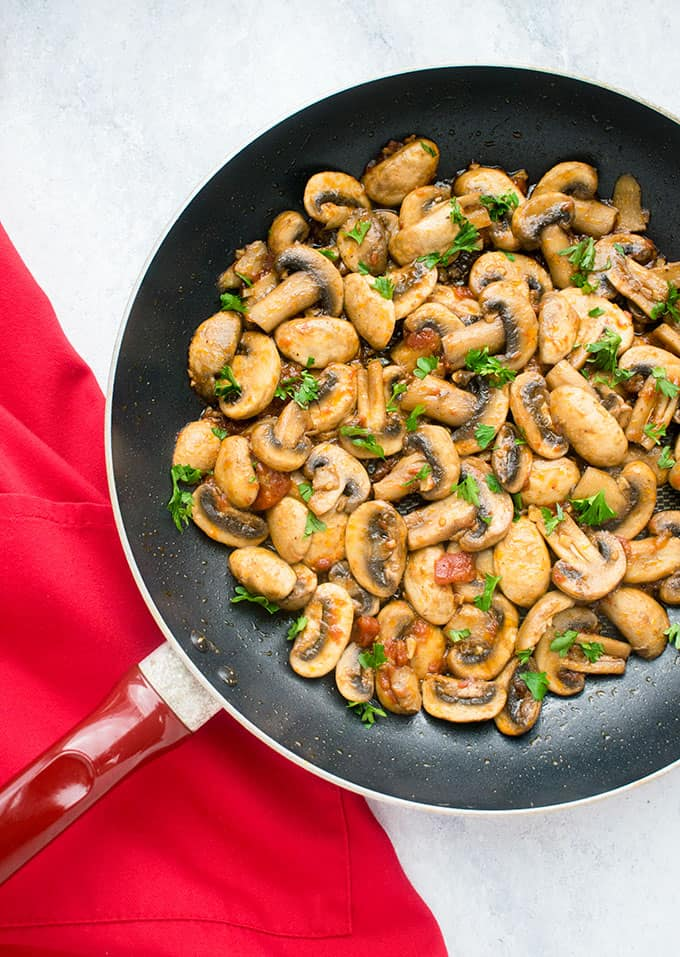 cooked mushrooms in frying pan, red apron