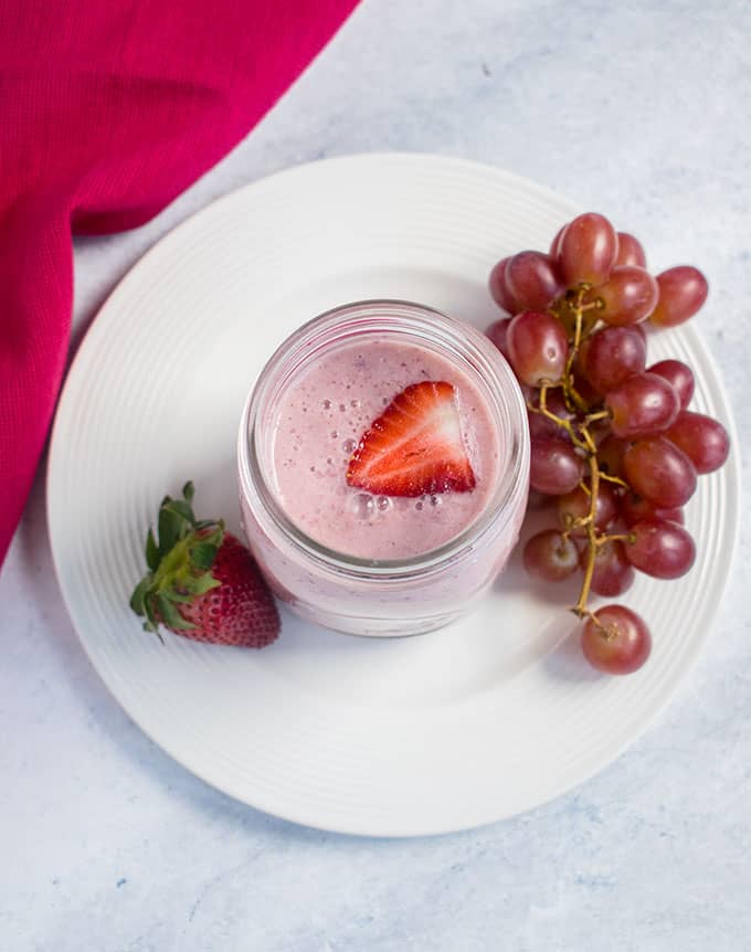 overhead of pink smoothie, grapes, strawberries, white plate, pink napkin