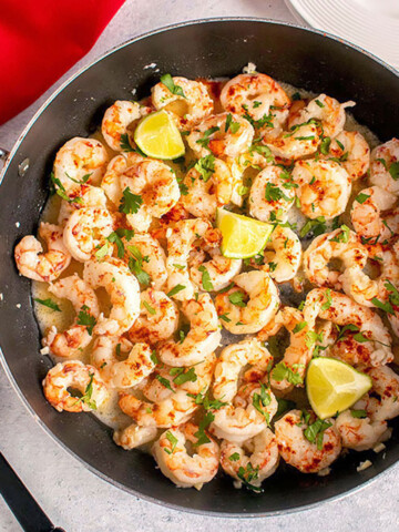 overhead view of shrimp in pan with lime, herbs