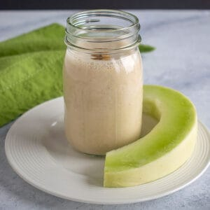 mason jar with smoothie and slice of honeydew, green napkin