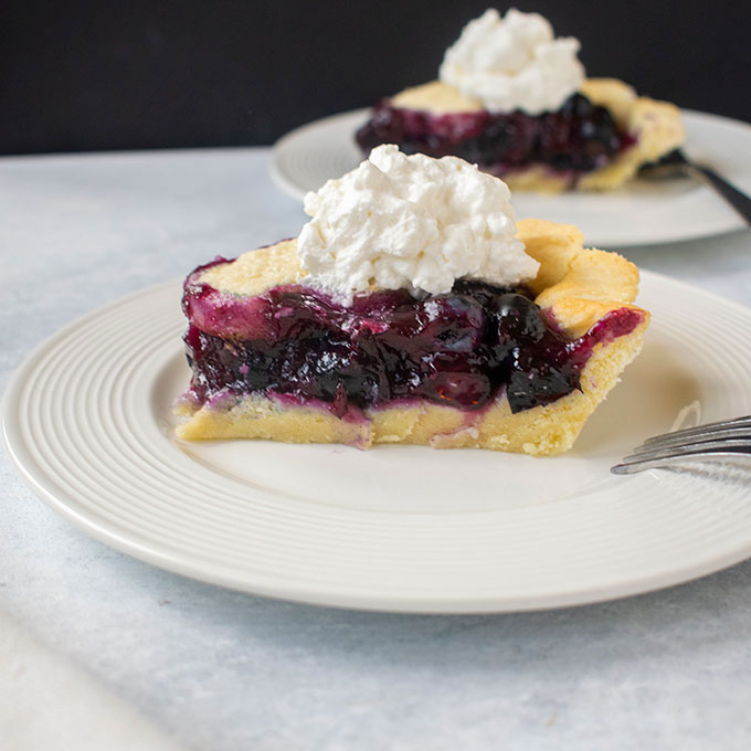 slices of blueberry pie with whipped cream