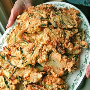 holding a platter of fried zucchini