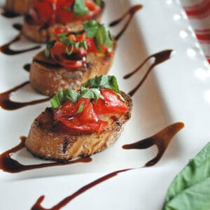 appetizer toasts on platter with tomatoes