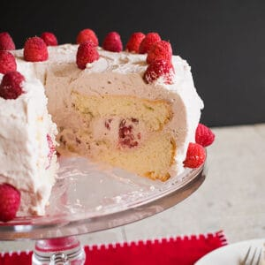 cake with whipped cream and raspberries on cake stand