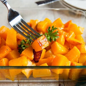 bowl of butternut squash cubes with one on a fork