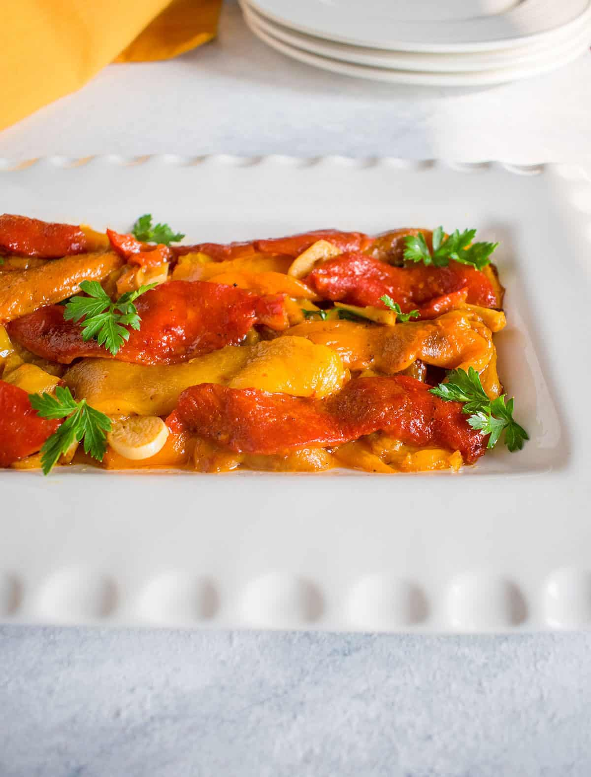 marinated roasted peppers on a white platter with garlic and parsley