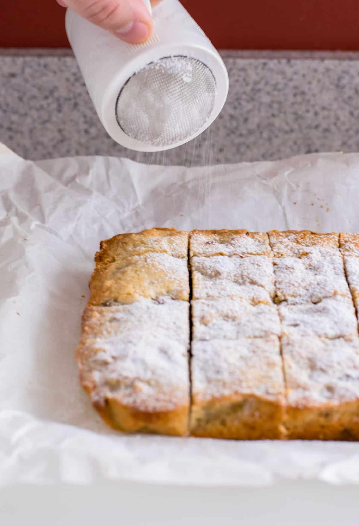 sprinkling confectioners sugar on date-nut bars