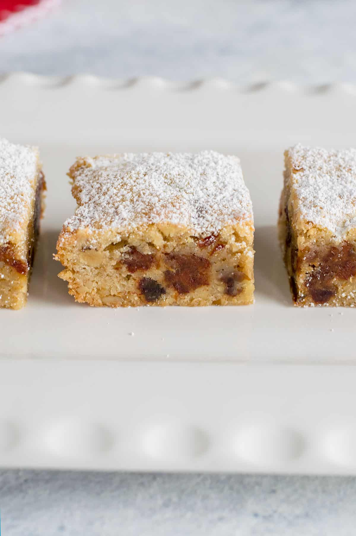 closeup of date-nut bars with powdered sugar on platter