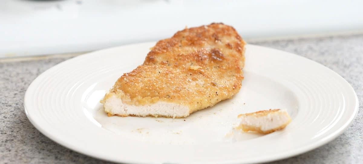 final breaded chicken cutlet cut open on plate