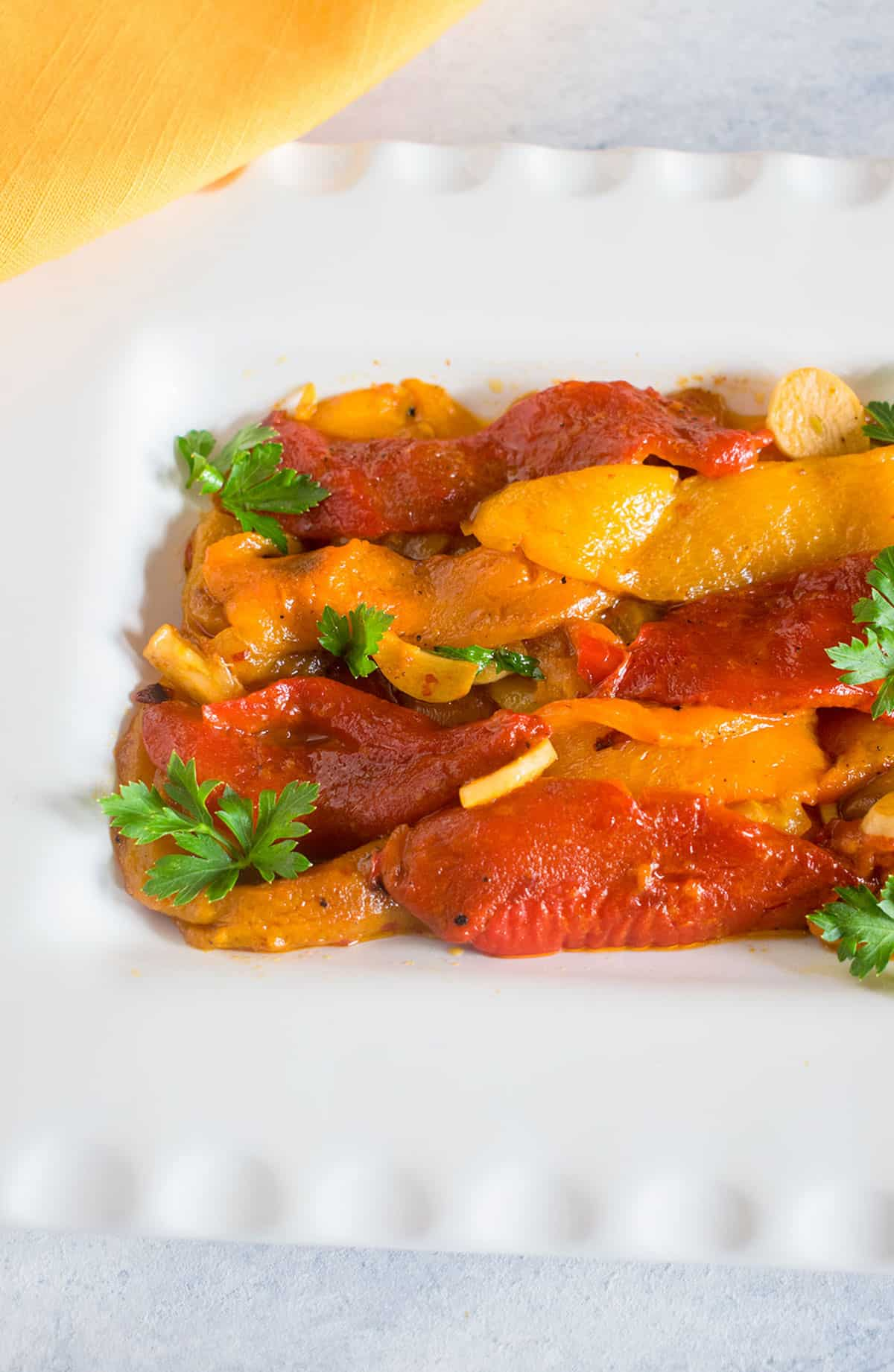 closeup of marinated roasted peppers with garlic and parsley