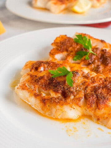 broiled cod on plate with parsley