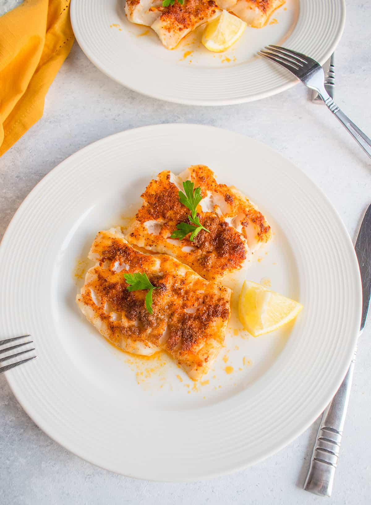 cod with paprika on two plates with lemon, silverware