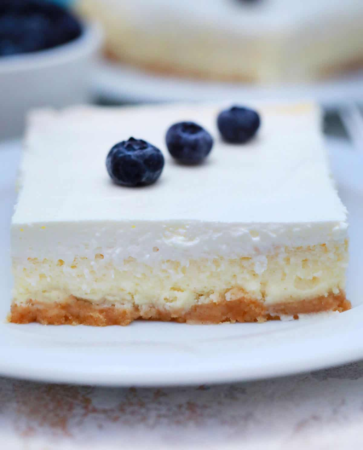 square slice of cheesecake with sour cream topping with three blueberries