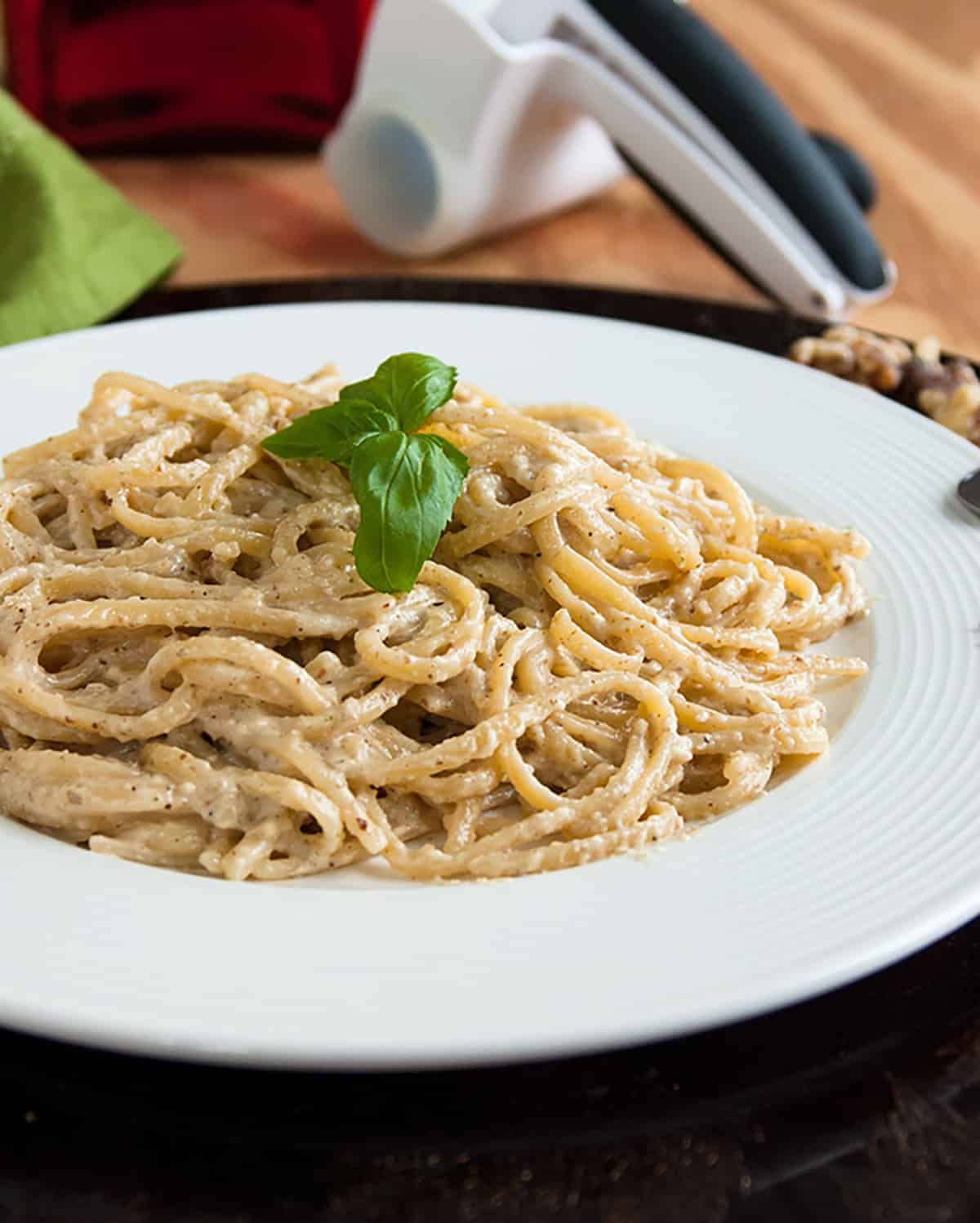 creamy linguine with walnuts, basil on white plate, cheese grater