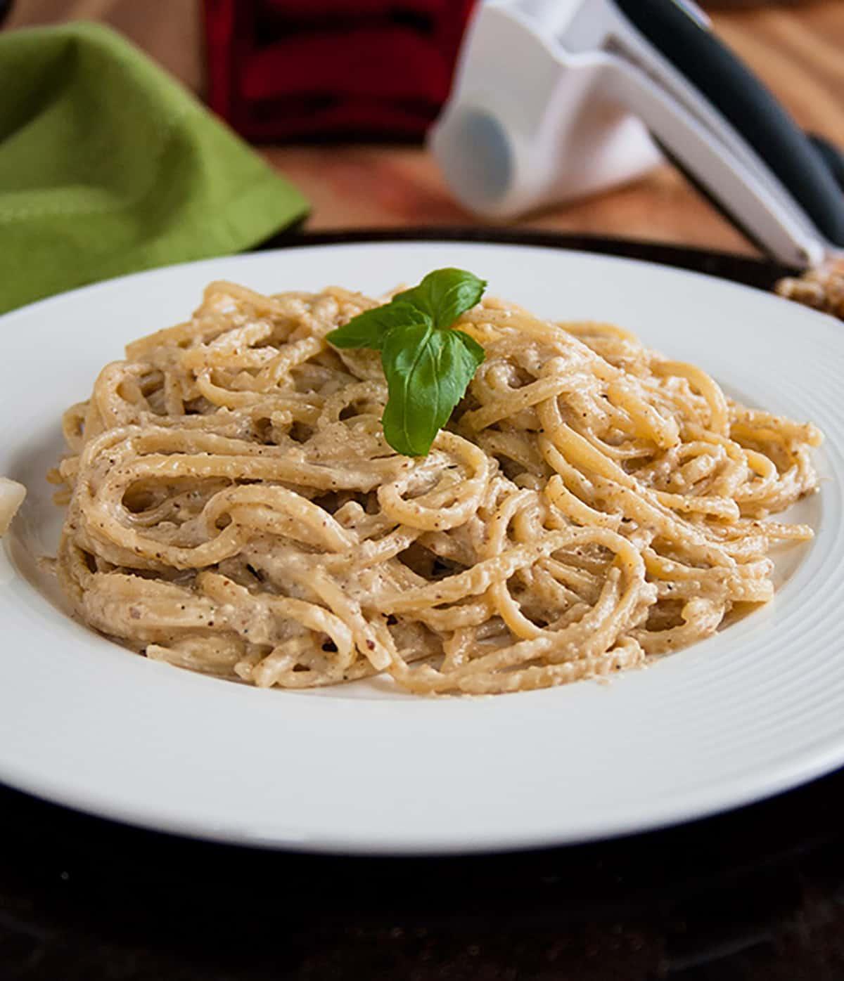 bowl of spaghetti with creamy sauce, basil