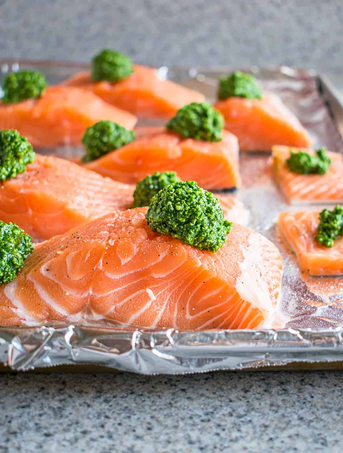 raw salmon with pesto on foil-lined sheet pan