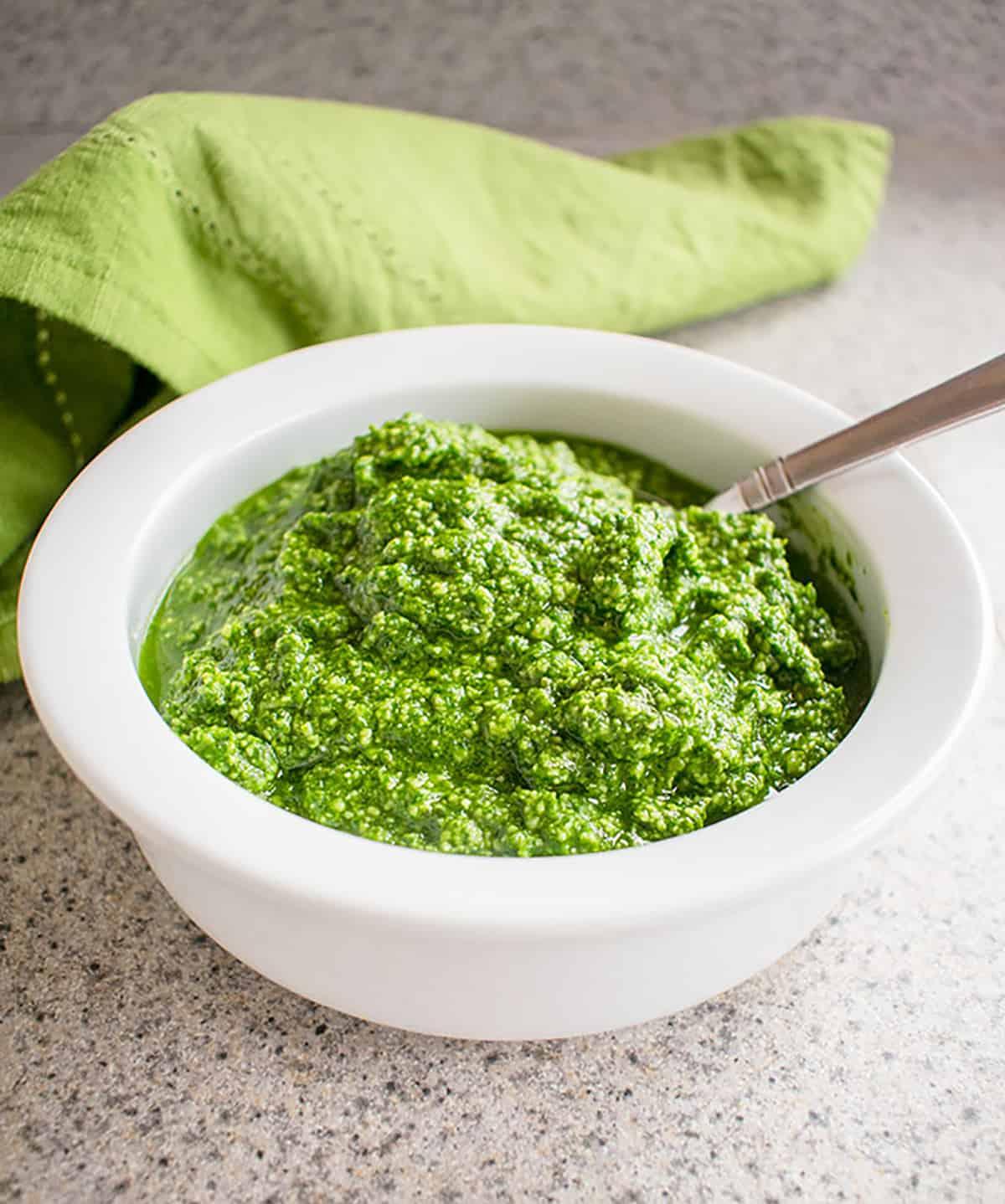 bowl of pesto with spoon, green napkin