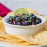 bowl of blueberry salsa with chips and lime