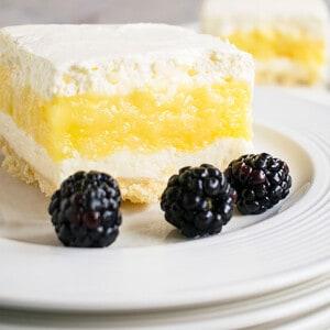 closeup of slice of lemon lush with blackberries