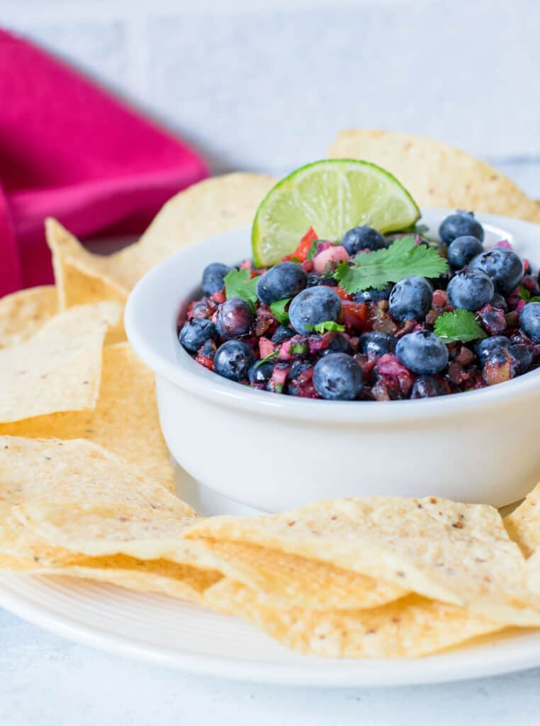 bowl of blueberry salsa with lime and tortilla chips