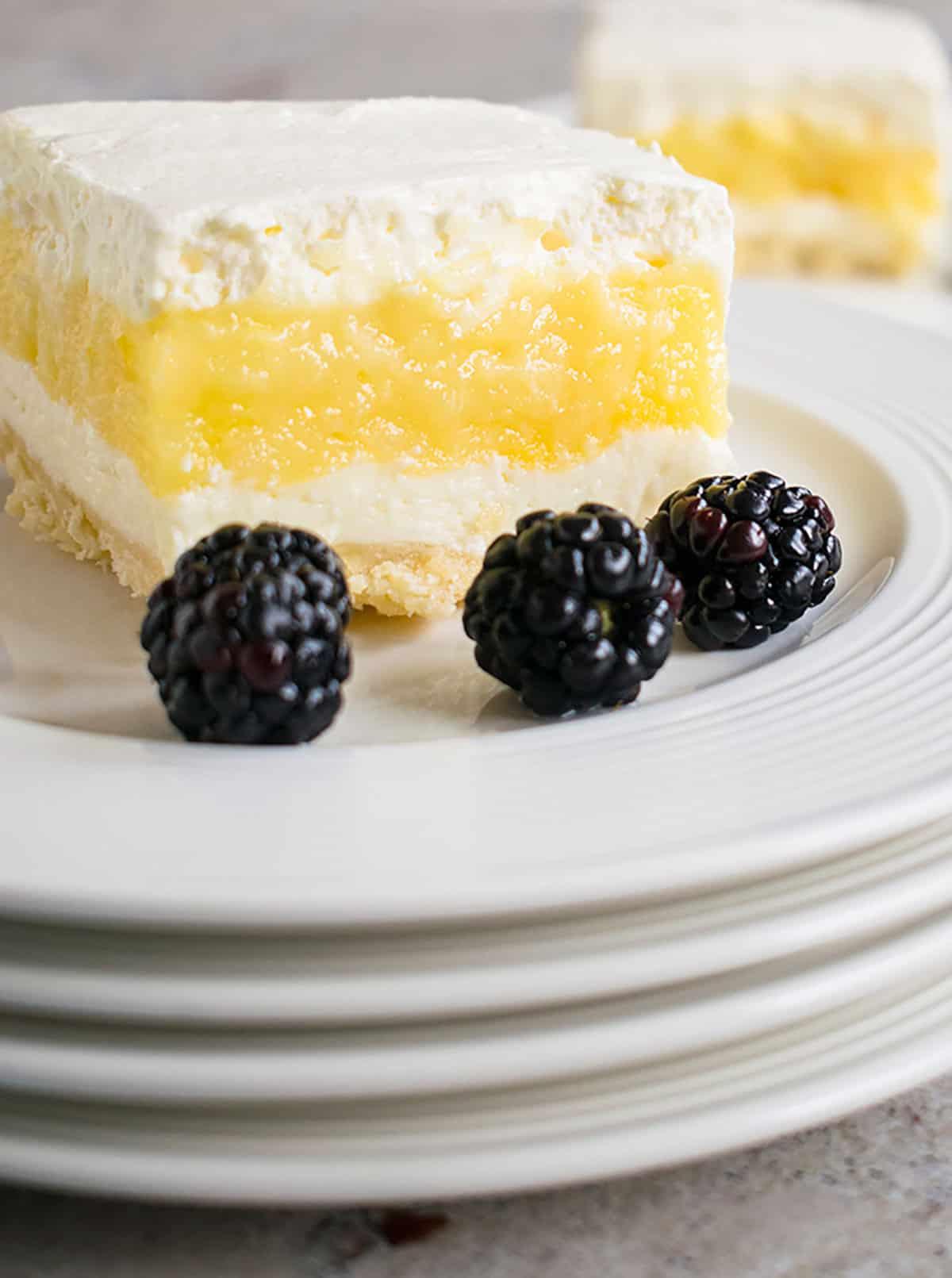 slice of lemon lush on stack of plates with blackberries