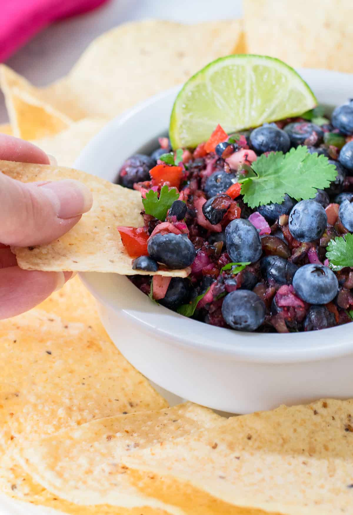 hand dipping tortilla chip into blueberry salsa