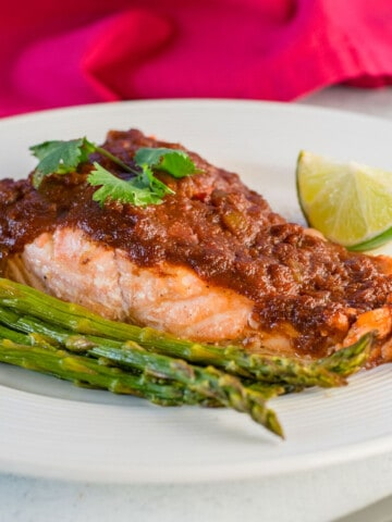 salmon with salsa, lime and asparagus on plate