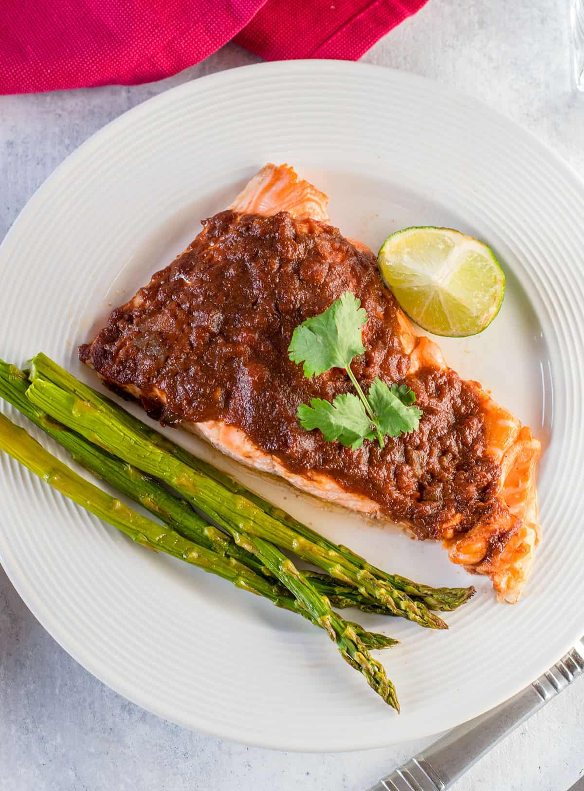 overhead view of salsa salmon on plate with lime and asparagus