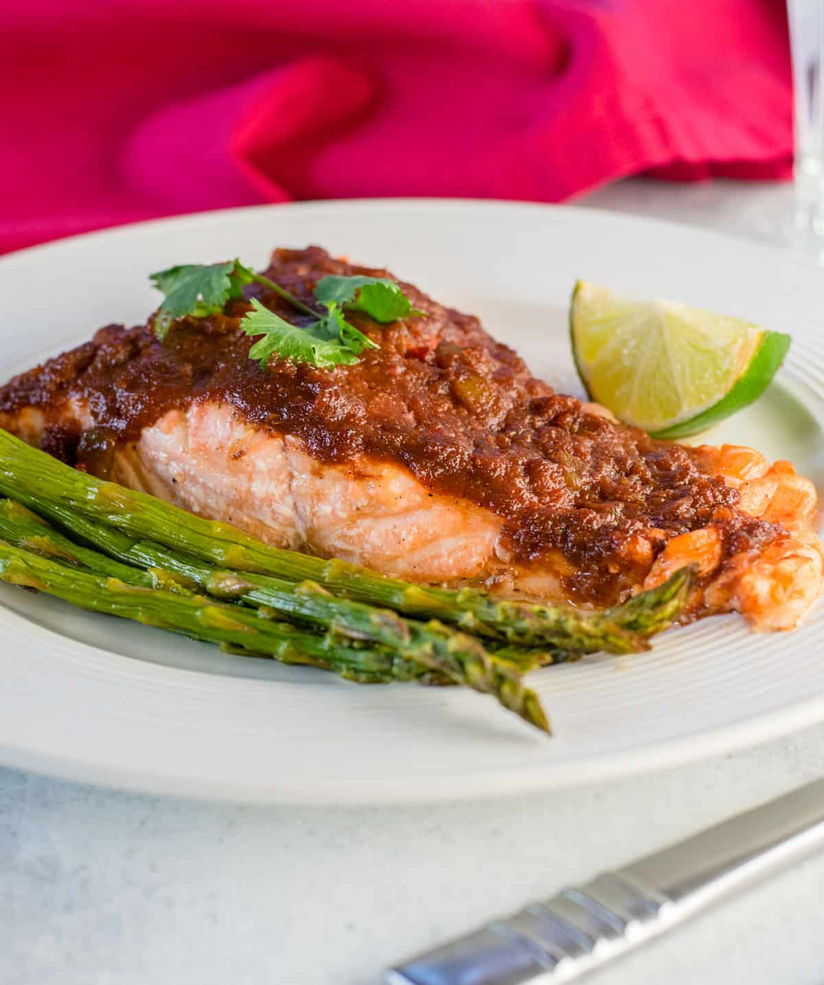 salmon with salsa and lime on plate with asparagus