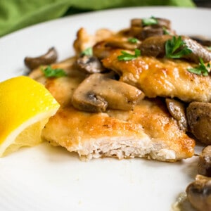 cut open piece of chicken marsala with mushrooms and lemon