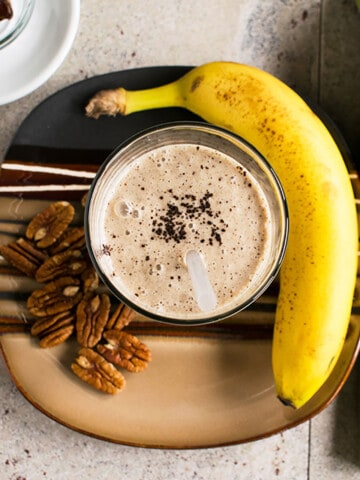 overhead view of smoothie with coffee grounds, banana, pecans