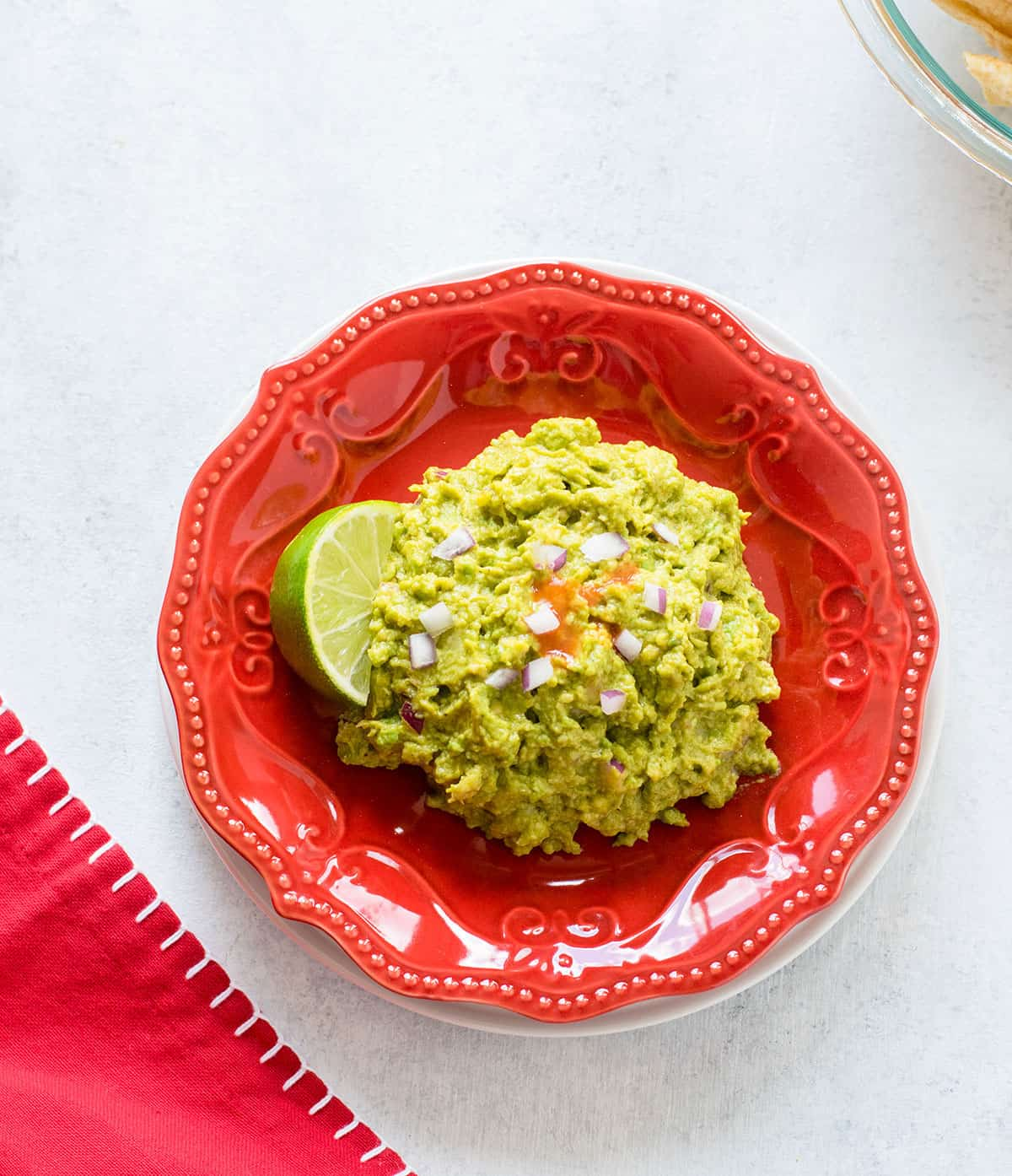 guacamole with lime on red plate