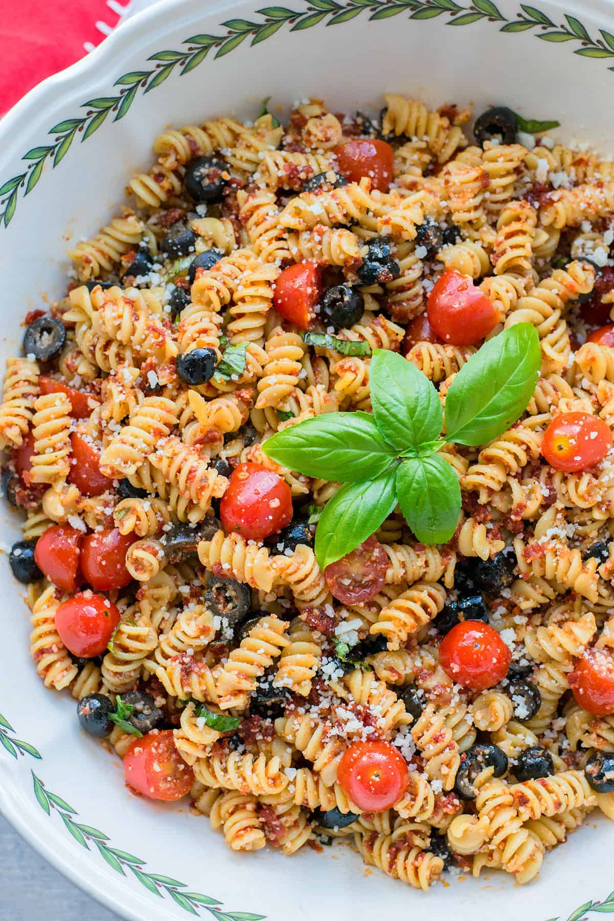 closeup of pasta salad with black olives, tomatoes and basil