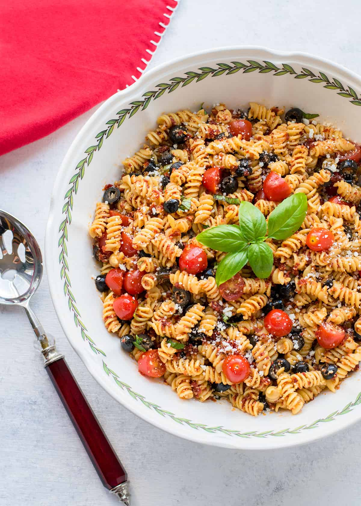 bowl of pasta salad with tomatoes, black olives, basil, Parmesan, serving spoon