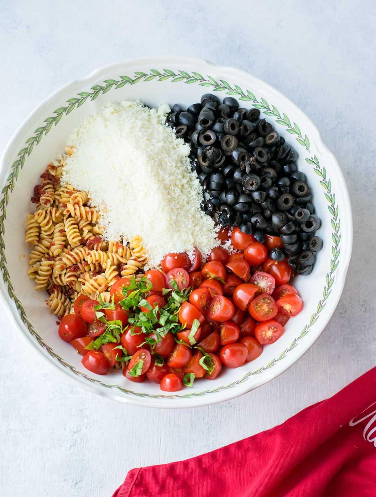 bowl of rotini pasta, Parmesan, black olives, tomatoes, basil