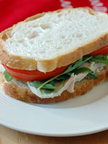 turkey sandwich with lettuce and tomato on plate