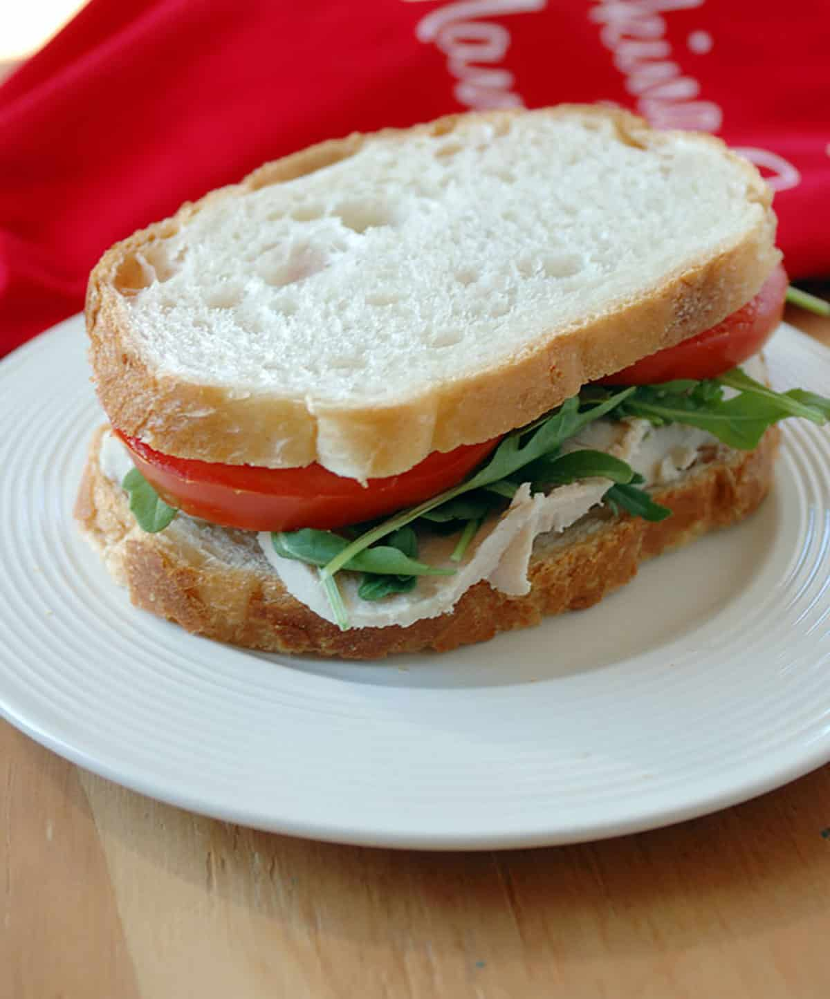 turkey sandwich with lettuce and tomato on white plate