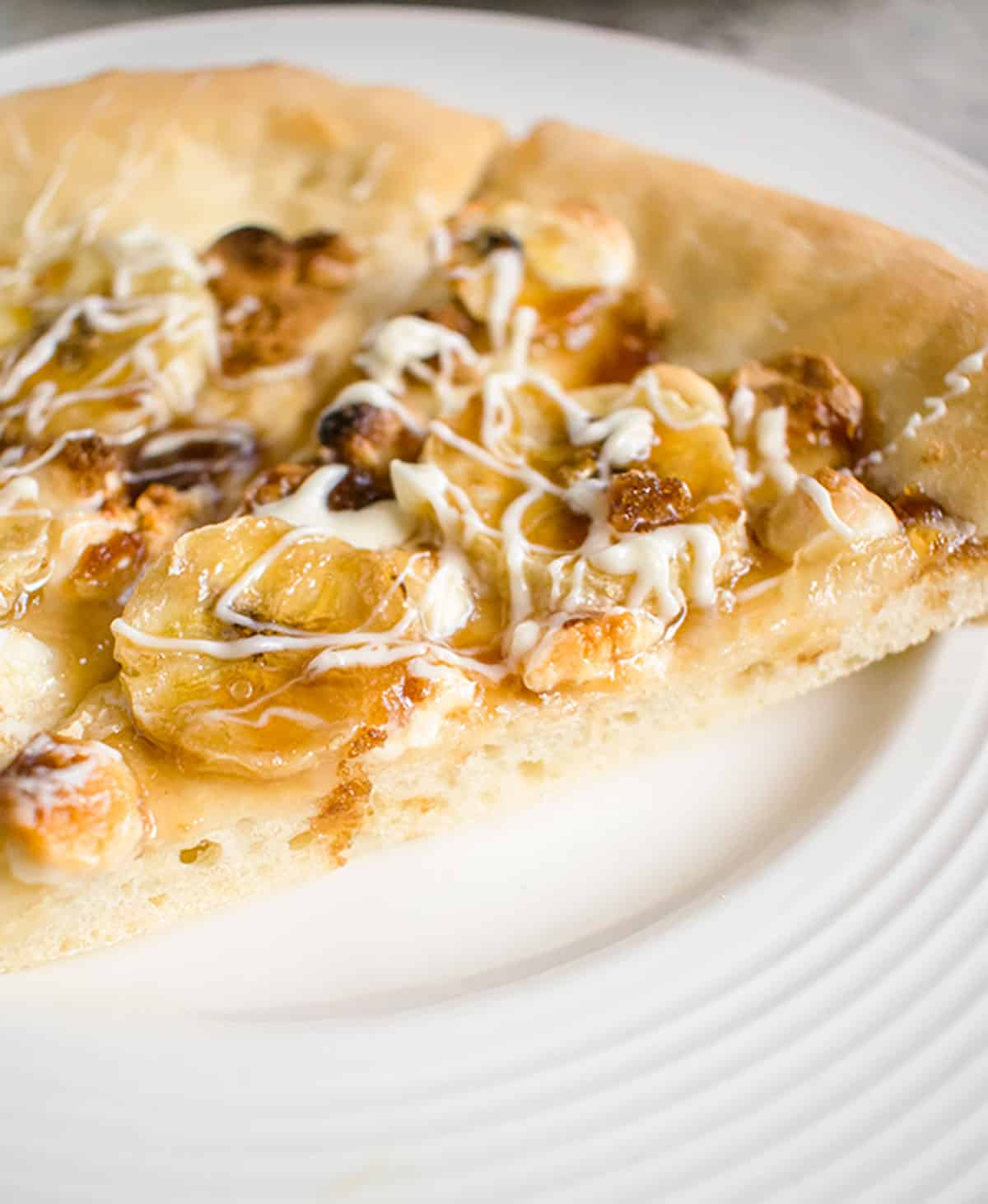closeup of pizza with sliced bananas, drizzled white chocolate