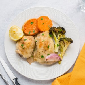 plate of roasted chicken thighs and vegetables with sweet potatoes