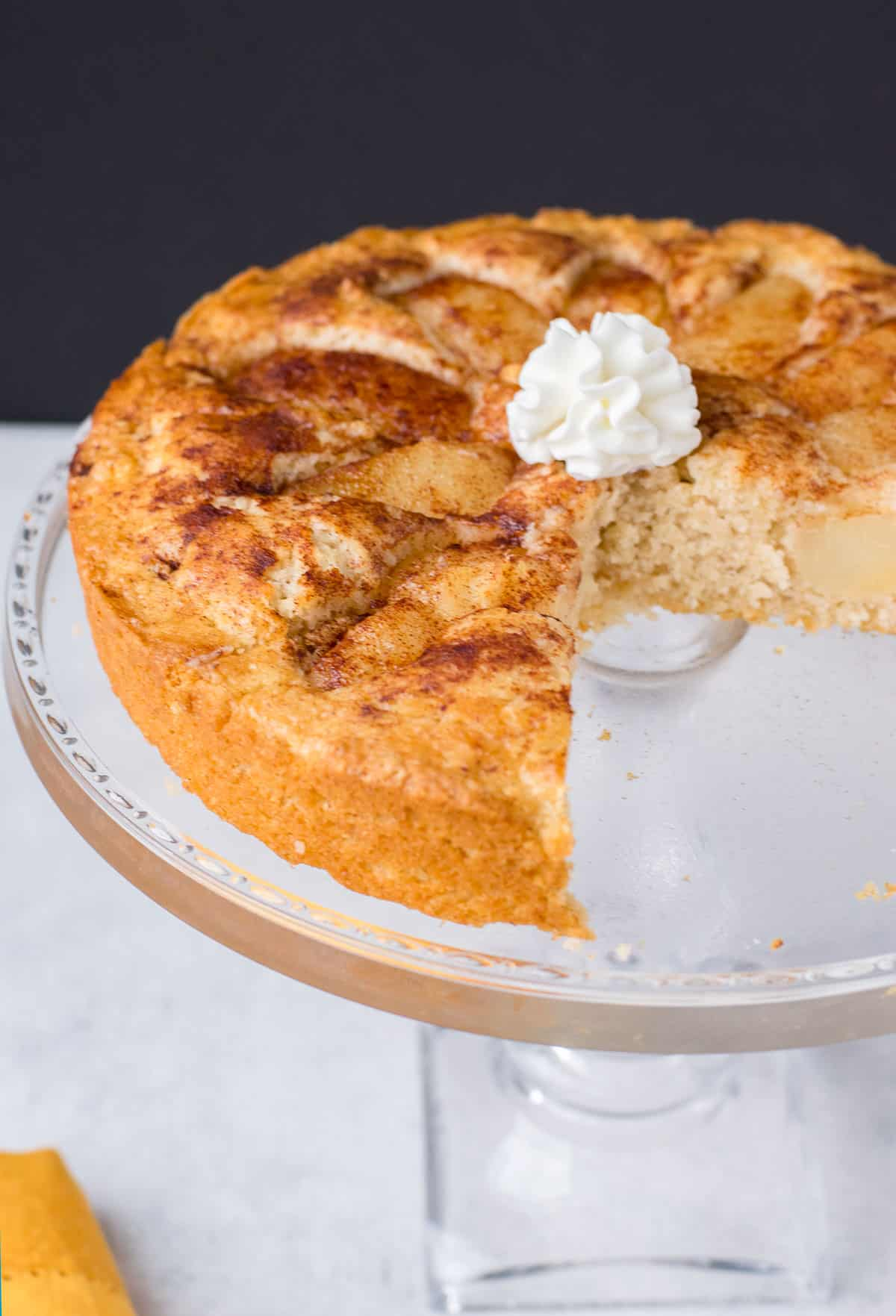 pear cake with whipped cream on glass cake stand