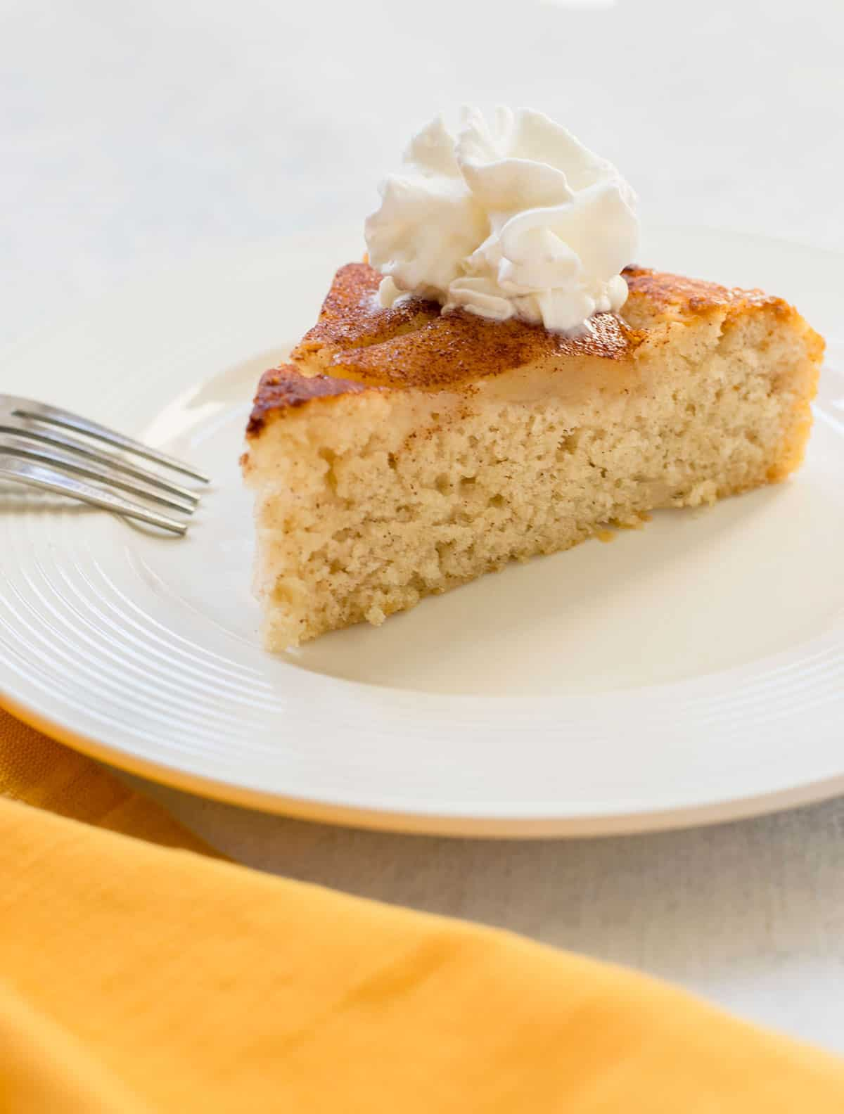slice of pear cake with cinnamon and whipped cream on white plate with fork